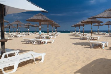 Rows of sun loungers and umbrellas on the beach.Tavira, Portugal