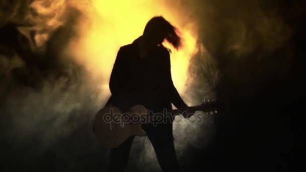 Dívka s kytarou v kouři a stroboskopy hraje heavy rock, metal