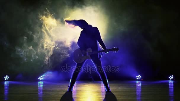 Girl with guitar in the smoke and strobe lights plays heavy rock, metal.