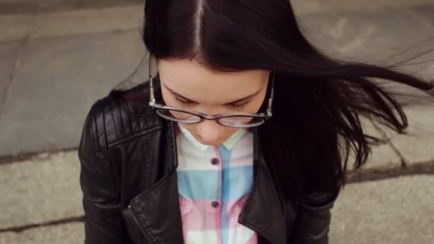 Gesicht des Mädchens mit Brille, dunkle Haare, close-up in Zeitlupe