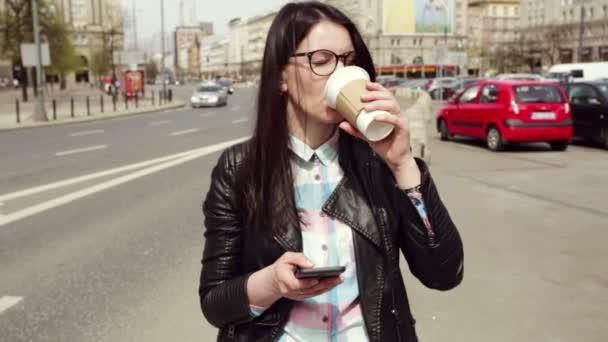 Das Mädchen steht in der Nähe der Straße gegen die Stadt und schaut auf sein Handy. Vorbeifahrende Autos