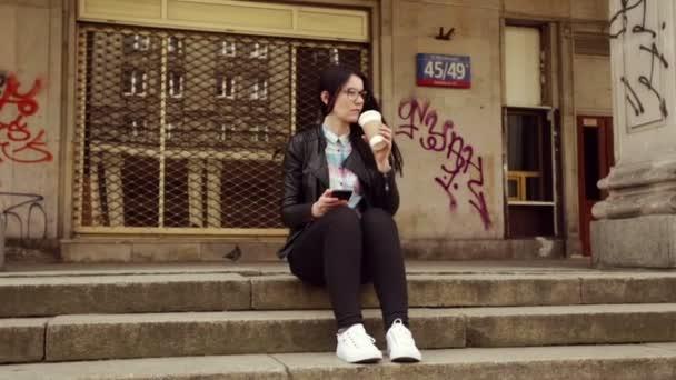 Hipster in Beton-Dschungel, Kaffee zu trinken und mit Blick auf seinem Smartphone. Soziale Netzwerke, Nachrichten