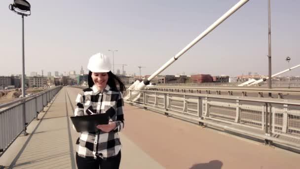 Žena v bílém stavbařskou přílbu a kostkovanou košili, stojící na visutý most a drží černou složku.