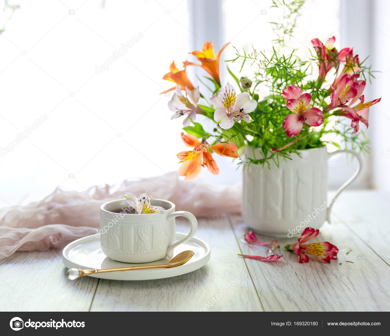 white cup with tea on the table flowers nearby stock photo
