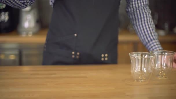 Barista helyezi a kávé az asztalon két csésze kávé
