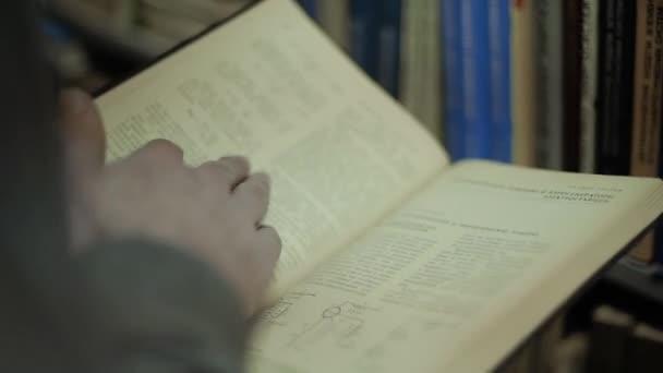 Muži otáčejí stránky ze staré knihy