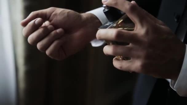 close up of handsome business man or groom using perfume or deodorant macro