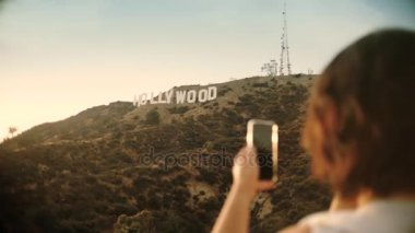 Tourist taking photograph of sunset in hollywood sign