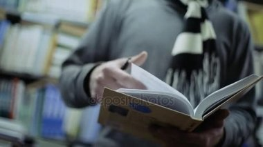Student reading a book in the library, close up