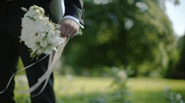 The groom holds a bouquet with ribbons in the wind, closeup