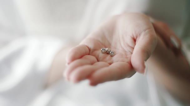 Nevěsta drží náušnice v ruce closeup