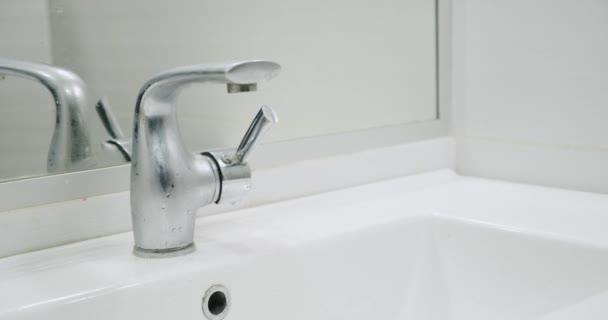 Mužská ruka otevře vodovodní kohoutek v koupelně. Detailní záběr obrazovky a mužská ruka. Zpomalený pohyb