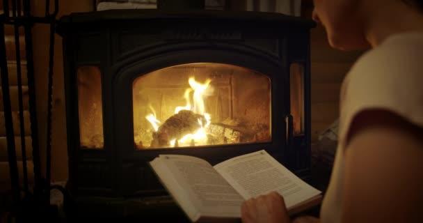 Pomalý pohyb, žena čte knihu u krbu. Uvolněná dovolená večer koncept. Střední střela
