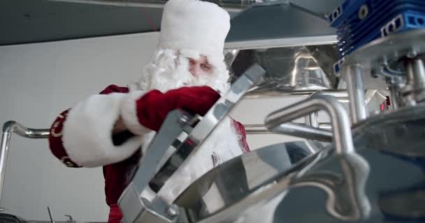 Santa Claus vaří pivo v řemeslném pivovaru, shazuje slad a chmel do plechovky od piva.
