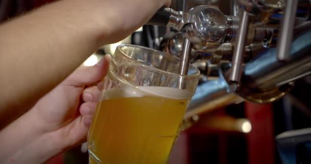Lassú mozgás. A csapos sört önt az üvegbe. közelről