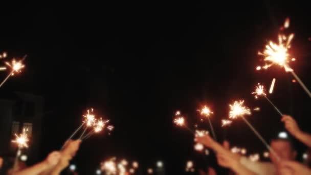 Svatební ohňostroj jiskra v rukou na svatební hosty drží světla de zaostřené a zpomalené