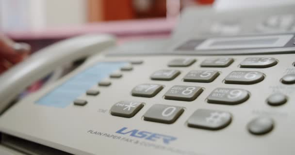 Hand einer Frau mit Fax, drückt die Taste und nimmt das Telefon in die Hand, Nahaufnahme
