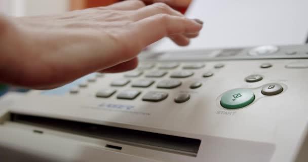 Nahaufnahme Hand einer Frau per Fax, drückt die Taste und nimmt das Telefon in die Hand,