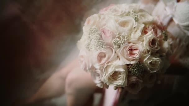 Ráno nevěsty v bílém peignoru drží v rukou svatební kytici růží. . Zavřít. Přesunout kameru