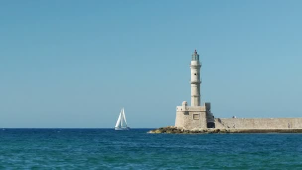 Sail boat passing by Chanias iconic lighthouse on a Summer day. Panning shot.