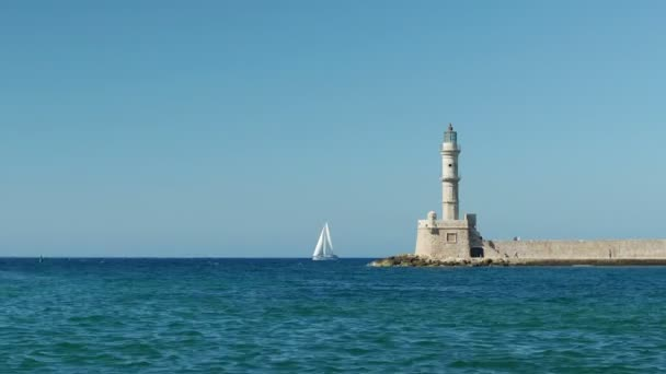 Sail boat passing by Chanias iconic lighthouse on a Summer day.