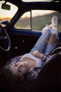 woman relaxing in vintage car