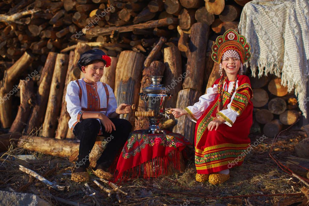 Sister and brother in Russian folk costumes sitting near samovar and laughing