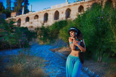 Charming girl in Arabic oriental costume on ancient ruins background dancing, smiling