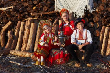 Three adorable kids in folk Russian costume and headdresses with samovar and in ancient shoes