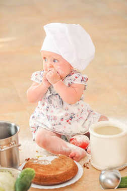 Cute liitle girl in chef's hat sitting on the kitchen floor soil