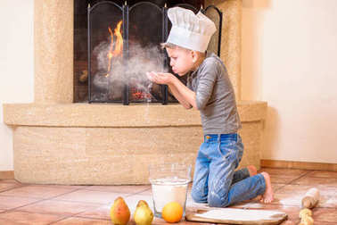 A boy in chef's hats near the fireplace sitting on the kitchen f