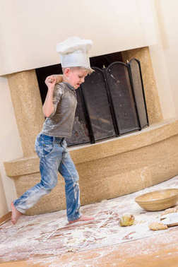 A boy in chef's hats near the fireplace standing on the kitchen