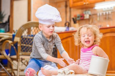 Two siblings - boy and girl - in chef's hats sitting on the kitc