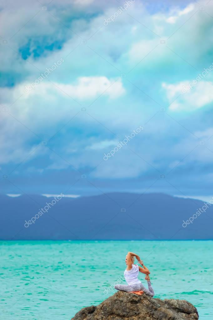 Beautiful mature aged woman sits on top of a cliff doing yoga.