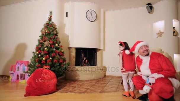 Dobrý nový rok Duch: vánoční strom, taštička, krb - táta, Dcera a starší syn pitvoří. Muž, oblečený jako Santa skákání na nafukovací hračka s dívka elf s malými rohy. Teenager je po nich