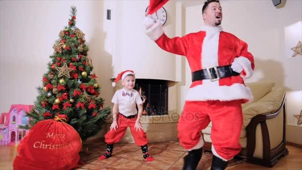 Dobrý nový rok Duch: vánoční strom, taštička, krb - muže a chlapce, plazení, hrát na blázna. Muž, oblečený jako Santa, blue eyed boy v motýlek, Santas červené víčko, červené kalhoty a vysoké ponožky je skákání, je to elf