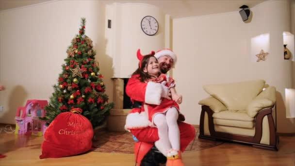 Gute Neujahrsstimmung: Weihnachtsbaum, Geschenktüte, Kamin - Papa und Tochter spielen den Narren. Ein als Weihnachtsmann verkleideter Mann springt auf einem aufblasbaren Spielzeug mit einer Elfenmädchen mit kleinen Hörnern. Kleine Junge-Elf folgt ihnen