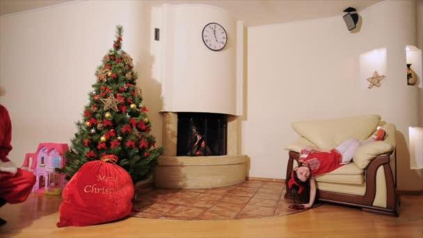Dobrý nový rok Duch: Santa Claus, vánoční strom, taštička, krb - svátečně oblečený roztomilá rodina slaví Vánoce, tanec před kamerou a hrát blázna