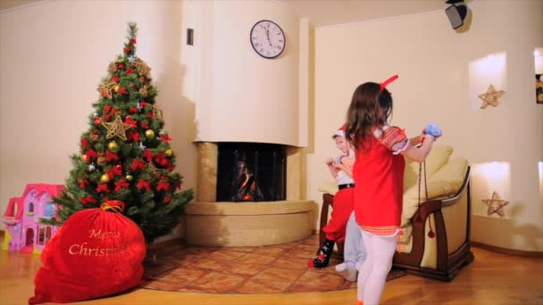 Good New Year spirit: Santa Claus, Christmas tree, gift bag, fireplace - festively dressed generation family celebrating winter holidays, dancing and fooling around in front of the camera.