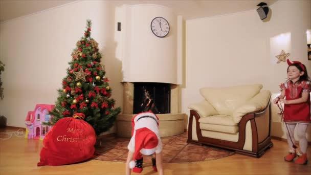 Jó újév szellemében: Mikulás, karácsonyfa, ajándék táska, kandalló - tobzódnak két generációs család ünnepli a téli ünnepek, a kamera előtt, játék bolond tánc