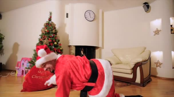 Good New Year spirit: Santa Claus, Christmas tree, gift bag, fireplace - festively dressed two generation family celebrating winter holidays, dancing in front of camera and playing fool.