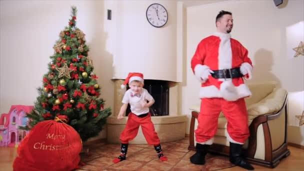 Gute Neujahrsstimmung: Christbaum, Geschenktüte, Kamin - Männer und Jungen spielen den Narren. Mann im Weihnachtsmannkostüm, blauäugiger Junge mit Fliege, Weihnachtsmannmütze, roter Hose und hohen Socken springt, er ist Elfe. Zeitlupe