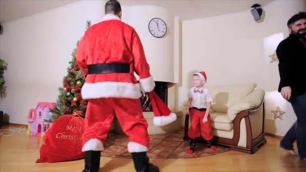 Weihnachtsbaum, Geschenktüte, Kamin - als Weihnachtsmann verkleidete Männer, Junge in roten Hosen und hohen Socken und ein Hipster in Samtjacke auf nacktem Oberkörper tanzen, spielen den Narren.
