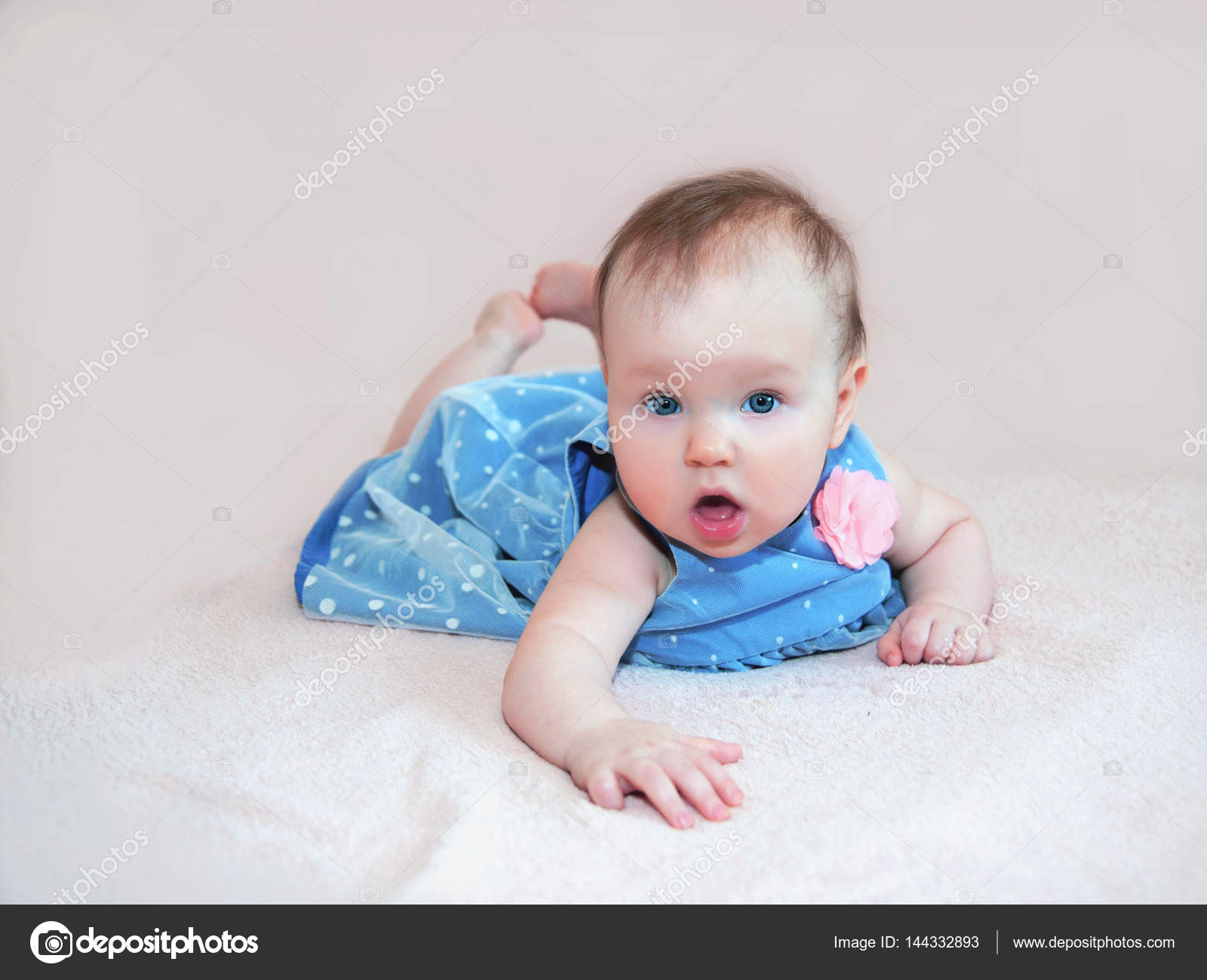 Cute Baby Girl In Blue Dress With Pink Flower Stock Photo