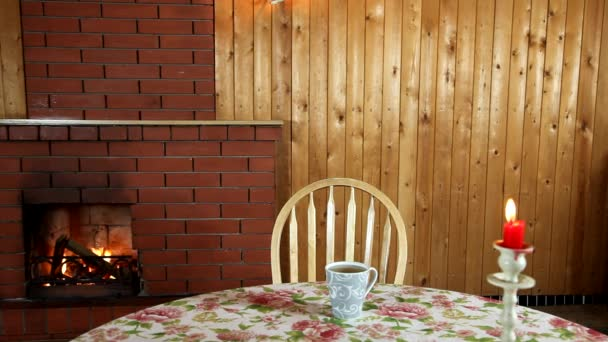 Cup of tea and burning candle on a table. Wooden chairs. Tablecloth with flowers. Interior room.