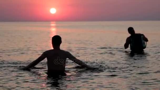 Sziluettjét az ember, aki megy a vízbe a háttérben a naplemente, a tenger felett. Megy a naplemente