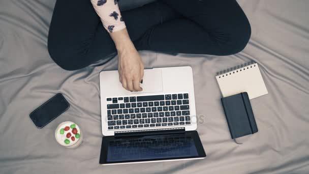 Pohled shora záběr ženy v posteli, nohy, laptop a jogurt na šedou deku