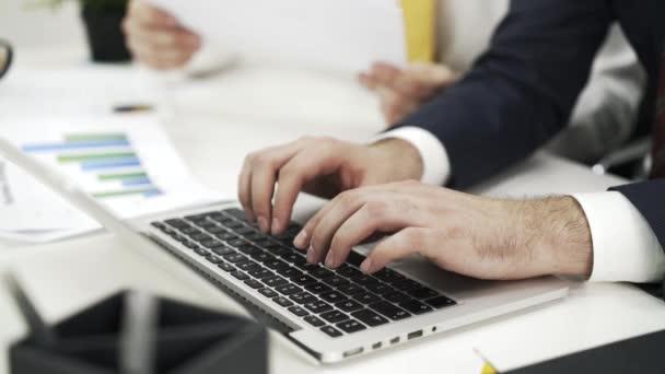 Muž psát na notebooku, spolupracovník zobrazující data