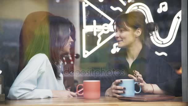 Két fiatal nő beszélt, és nevetve egy kávézóban