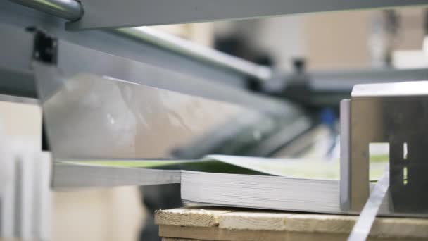 Pan shot of posters being printed at industrial printer